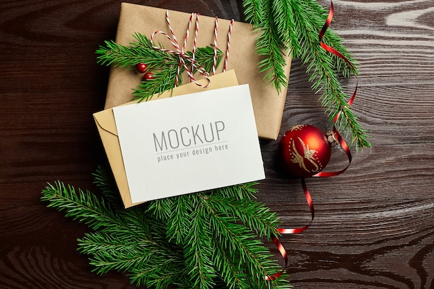 Greeting card mockup with gift box, red christmas decorations and fir tree branches