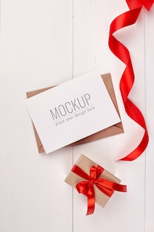 Greeting card mockup with gift box and red ribbon
