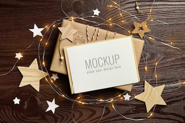 Greeting card mockup with gift box, wooden decorations and christmas lights