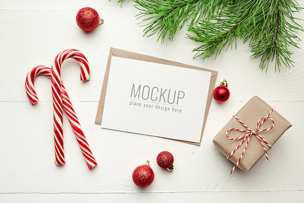 Greeting card mockup with gift boxes, candy canes and christmas decorations