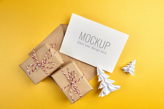 Greeting card mockup with gift boxes and paper christmas trees