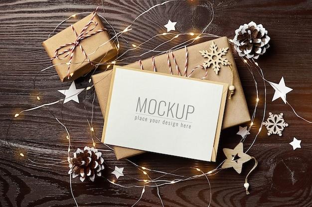 선물 상자, 소나무 콘, 나무 장식 및 크리스마스 조명이있는 인사말 카드 모형