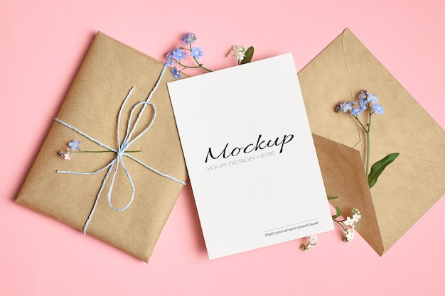 Greeting card mockup with gift, envelope and spring forget-me-not flowers on pink