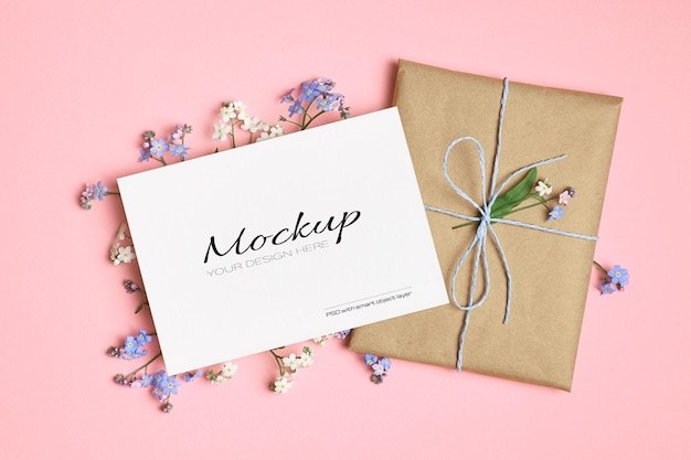Greeting card mockup with gift and spring forget-me-not flowers on pink