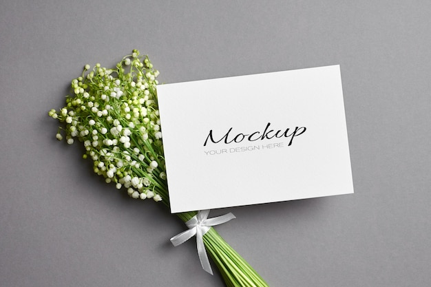 Greeting card mockup with lily of the valley flowers bouquet on grey