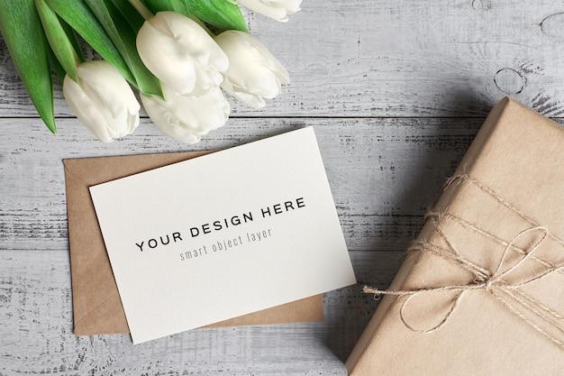 木製の背景にチューリップの花とギフトボックスとグリーティングカードのモックアップ