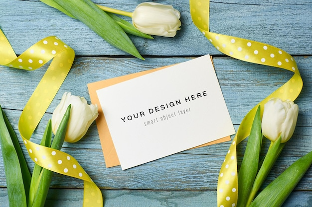 Greeting card mockup with tulip flowers on blue wooden background