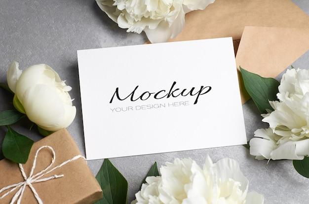회색에 봉투, 선물 상자, 흰색 모란 꽃이 있는 인사말 카드 또는 초대 모형