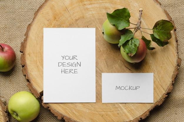 素朴なスタイルと自然のベージュ色の背景にリンゴとグリーティングカードや結婚式の招待状のモックアップ Premium Psd