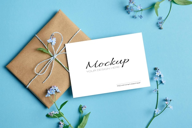 Greeting card stationary mockup with gift and spring forget-me-not flowers