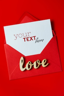 Greeting card for valentine's day. red envelope with blank white paper. mockup of love letter.