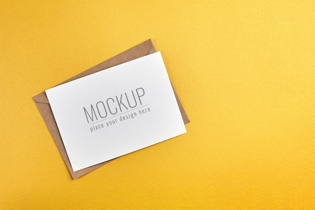 金の紙の背景に封筒のモックアップとグリーティングカード