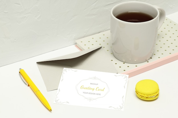 ノート、封筒、ペン、マカロン、紅茶のカップ付きグリーティングカード