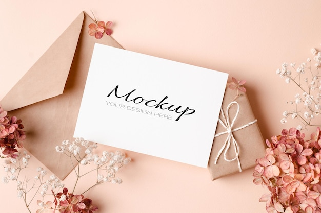 Greeting or invitation or card mockup with gift box, envelope and pink hydrangea flowers