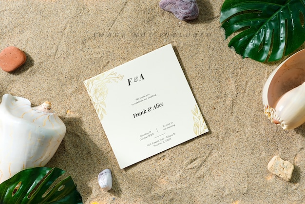 Greeting mockup card on a sand beach with shells and leaves.