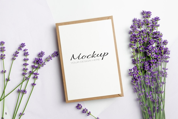 Макет поздравительной или пригласительной открытки с конвертом и свежими цветами лаванды на белом