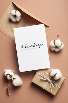 封筒、ギフト ボックス、綿の花の装飾が施されたグリーティング カードまたは招待状カードのモックアップ