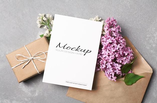 Макет поздравительной или пригласительной открытки с подарочной коробкой, конвертом и весенними цветами сирени