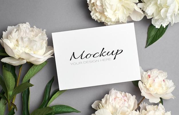 Макет поздравительной или пригласительной открытки с белыми цветами пиона на сером