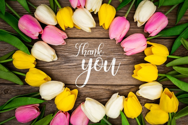 Greeting template with tulips on a wooden background