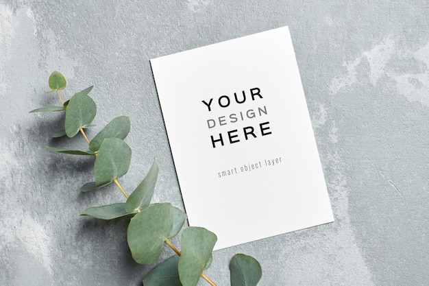Greeting and wedding invitation card mockup with fresh eucalyptus twigs