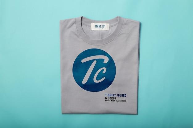 파란색 배경에 디자인을위한 회색 접힌 티셔츠 모형 템플릿