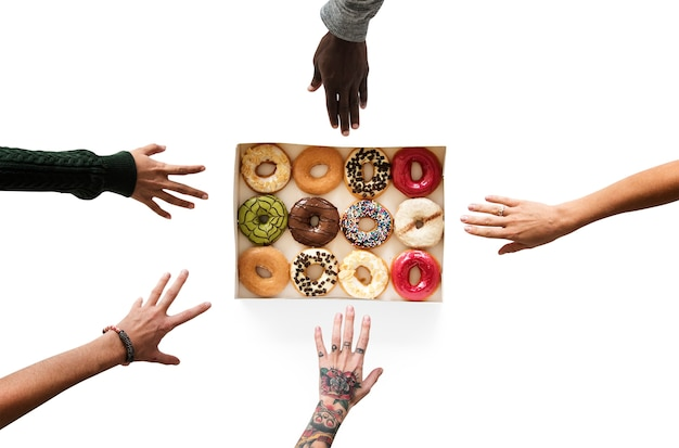 Group of hands reaching sweeten donut dessert