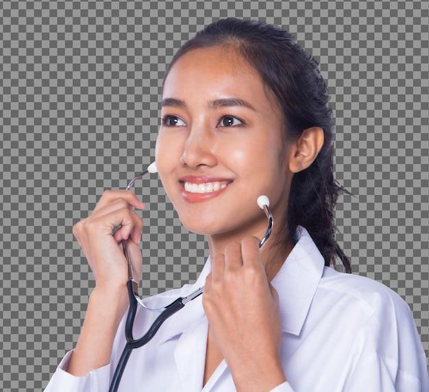 제복을 입은 검은 머리를 한 20대 아시아 의사 여성의 반신은 청진기를 적용하고 큰 미소를 지으며 검게 그을린 피부 간호사는 의료 병원, 스튜디오 조명 흰색 배경에서 행복한 미소를 표현합니다.