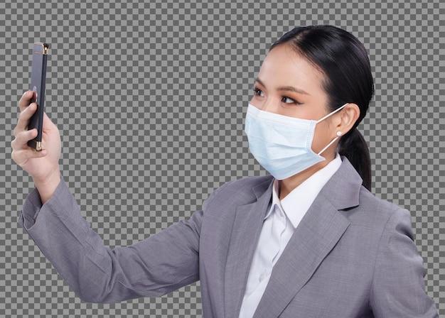 Половина тела портрета 20-х годов азиатская женщина черные волосы белая рубашка костюм носить маску с помощью изолированного смарт-телефона. офисная девушка использует цифровой планшет, умный мобильный телефон для бизнеса, носит защитную маску для лица
