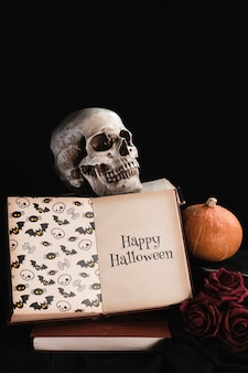 Halloween concept with skull and book on black background
