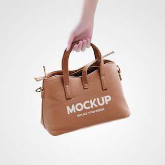 Рука держать модный мешок макет