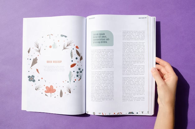 Рука держит журнал на фиолетовом фоне