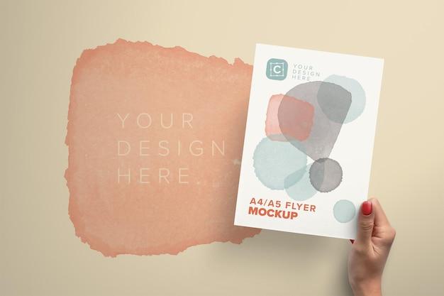 Рука держит макет бумаги a4a5 с редактируемым фоном