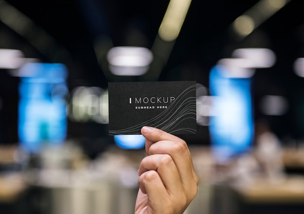 Hand holding a black business card mockup