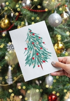 クリスマスホリデーグリーティングデザインモックアップカードを持っている手