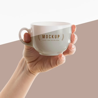 Hand holding a cup mock-up