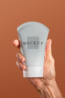 Hand holding a facial cream tube container mockup