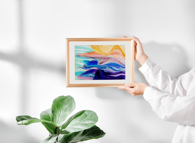 Hand holding framed painting mockup in living room and window shadow on white wall.