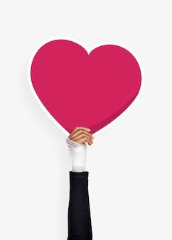 Hand holding a heart cardboard prop