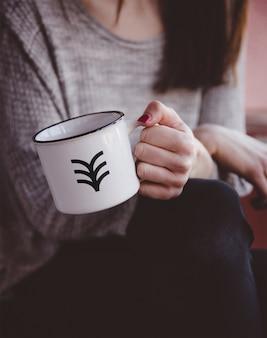 Hand holding metal mug