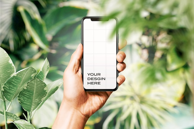 Hand holding new smartphone mockup surrounded by leaves
