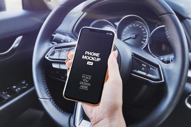 Hand holding phone in car salon mockup
