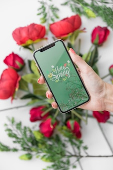 Hand holding smartphone mockup above flowers