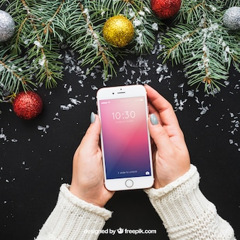 Hand holding smartphone mockup with christmas design