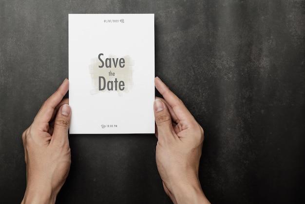 結婚式の招待カードのモックアップを持っている手、カードテンプレートをご覧ください。