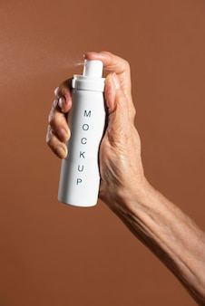 Hand holding a white aerosol spray bottle mockup