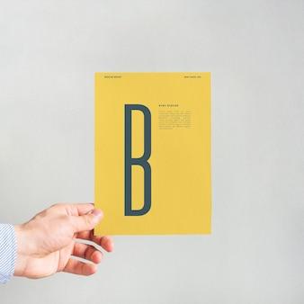 Hand holding yellow paper mockup