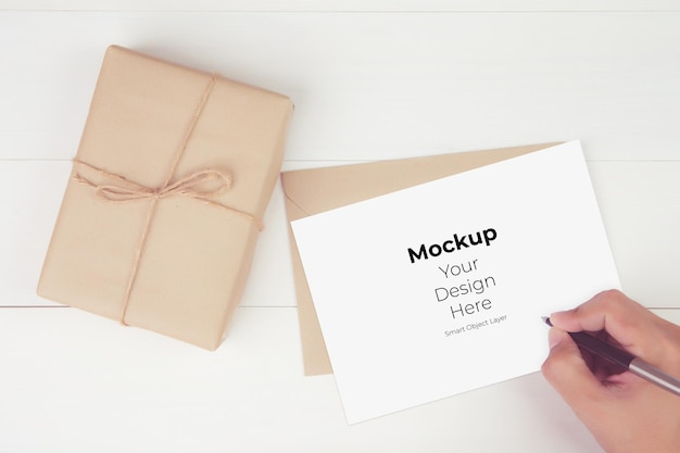 Hand of man writing letter with blank greeting card mockup