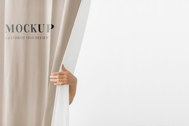 Hand opening a brown curtain mockup