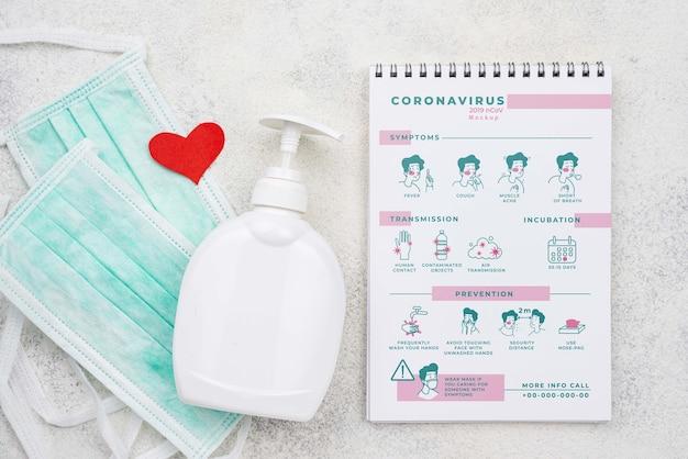 Hand sanitizer and medical masks beside notebook
